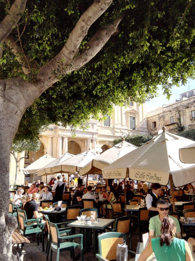Hangulatos tér utcazenészekkel és éttermekkel Málta fővárosában