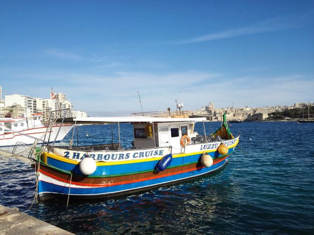Klasszikus máltai hajó háttérben Vallettával